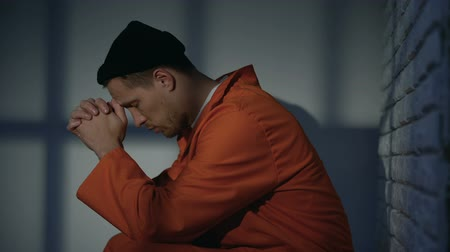 гангстер : Caucasian imprisoned male praying in cell, feeling guilty and asking for mercy Стоковые видеозаписи