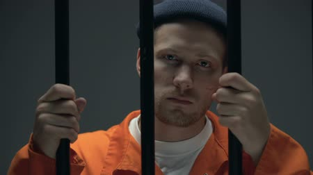areszt : Imprisoned male holding bars and looking to camera, feeling guilty and desperate