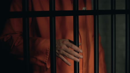mafia : Aggressive male prisoner holding bars with injured hands, violence in jail Stock Footage