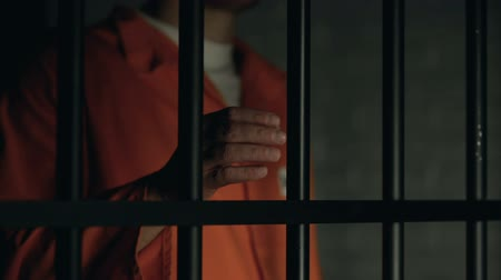 ethic : Help word written on prisoner fingers, male holding jail bars, ill treatment Stock Footage