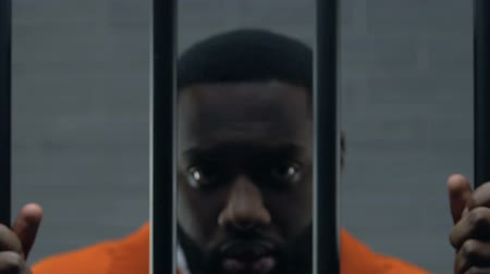 заключенный : Upset Afro-American prisoner holding bars in cell and looking at camera, guilty