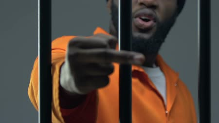 remand : Angry Afro-American criminal showing middle finger through prison cell, conflict