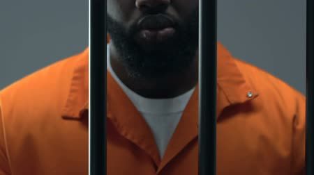 kafes : Afro-American prisoner in handcuffs feeling sorrow about made crime, guilty Stok Video
