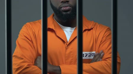 remand : Black criminal with hands crossed standing in prison cell, waiting for judgment