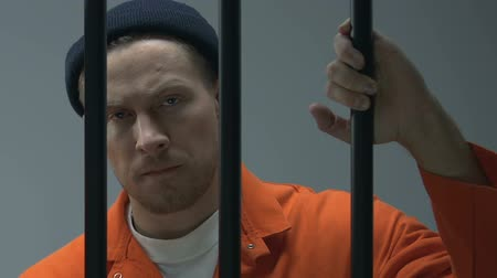 заключенный : Caucasian criminal looking at camera through prison bars, waiting for judgment