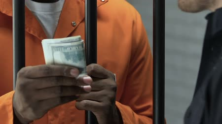 hapsedilme : Afro-American criminal giving money as bribe to prison guard, breaking law