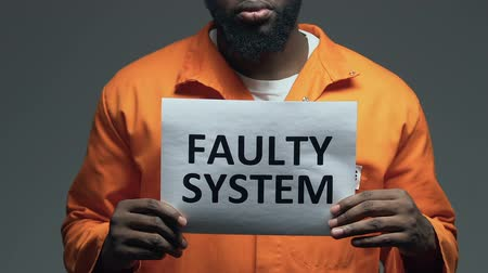 hapsedilme : Faulty system phrase on cardboard in hands of Afro-American prisoner, disorder