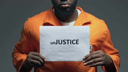 jurisdiction : Injustice word on cardboard in hands of African-American prisoner, disorder