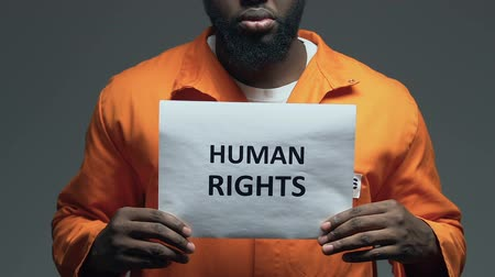 hapsedilme : Human rights phrase on cardboard in hands of African-American prisoner, assault Stok Video