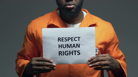 jurisdiction : Respect human rights phrase on cardboard in hands of Afro-American prisoner