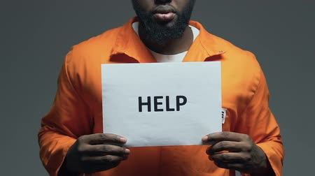 jurisdiction : Help word on cardboard in hands of Afro-American prisoner, asking for freedom