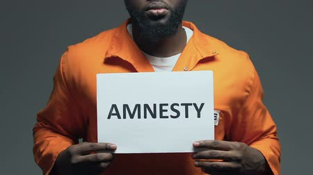regras : Amnesty word on cardboard in hands of Afro-American prisoner, forgiveness
