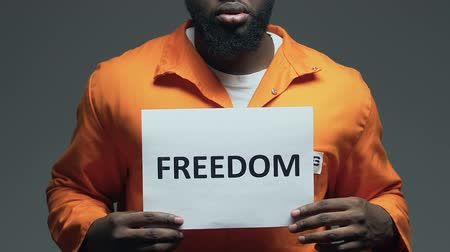 jurisdiction : Freedom word on cardboard in hands of Afro-American prisoner, asking for amnesty