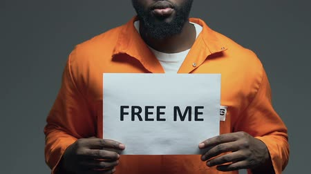 jurisdiction : Free me phrase on cardboard in hands of Afro-American prisoner, amnesty asking Stock Footage
