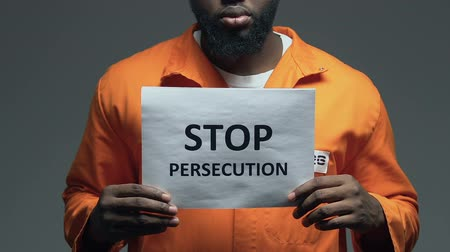 судья : Stop persecution phrase on cardboard in hands of Afro-American prisoner, assault Стоковые видеозаписи