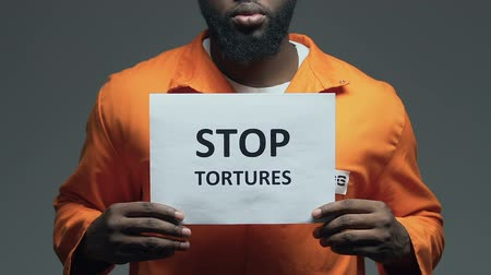 perseguição : Stop tortures phrase on cardboard in hands of Afro-American prisoner.