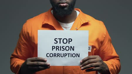frase : Stop prison corruption phrase on cardboard in hands of black prisoner, disorder