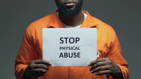 frase : Stop physical abuse phrase on cardboard in hands of black prisoner, assault