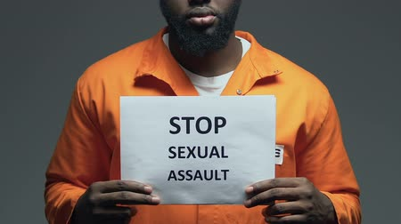 frase : Stop sexual assault phrase on cardboard in hands of black prisoner, raping