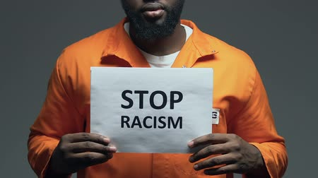 üldözés : Stop racism phrase on cardboard in hands of black prisoner, discrimination Stock mozgókép