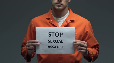 jurisdiction : Stop sexual assault phrase on cardboard in hands of Caucasian prisoner, raping