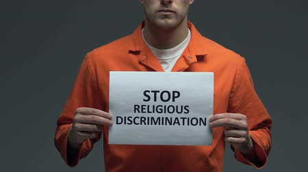perseguição : Stop religious discrimination phrase on card in hands of Caucasian prisoner