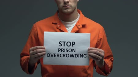jurisdiction : Stop prison overcrowding phrase on cardboard in hands of Caucasian prisoner Stock Footage