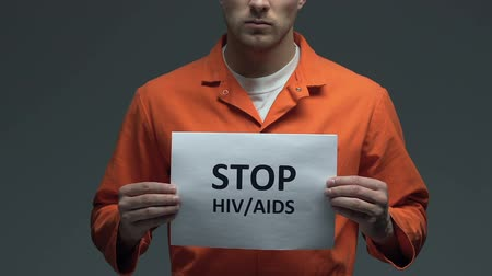 imprison : Stop HIV AIDS phrase on card in hands of Caucasian prisoner, proper treatment