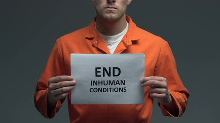 jurisdiction : End inhuman conditions phrase on card in hands of Caucasian prisoner, protest Stock Footage