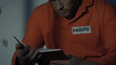 imprison : Lonely Caucasian prisoner reading book in cell, leisure time in prison, closeup Stock Footage