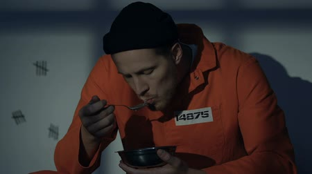 hapsedilme : Hungry Caucasian prisoner eating meal in cell, awful disgusting food, conditions