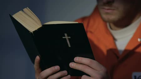 vazba : Prisoner in handcuffs reading holy bible, repentance for sins, belief and hope