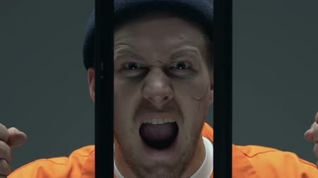 заключенный : Upset criminal with scars on face holding prison bars, regretting about past Стоковые видеозаписи