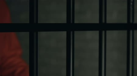cruelty : Criminal with beaten hands standing behind prison bars, conflicts in jail Stock Footage