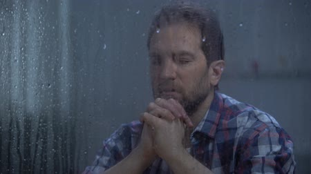 sinner : Hopeless male praying God behind rainy window, asking for help and forgiveness