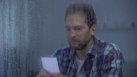 без вести пропавшие : Upset divorced man looking at family photo on rainy day, missing wife and kids