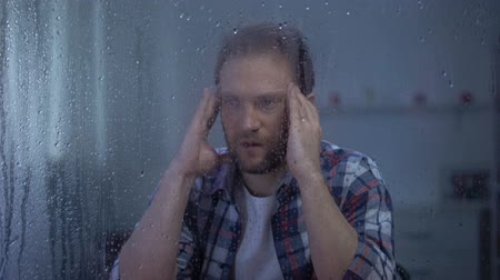 меланхолия : Depressed man massaging temples behind rainy window, suffering from head ache