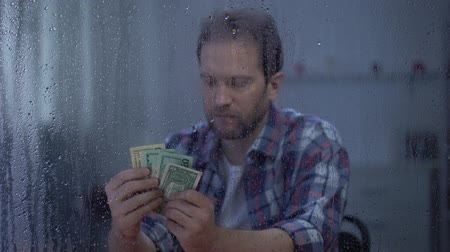 attitude : Middle-aged man counting money behind rainy window, poor budget, poverty Stock Footage