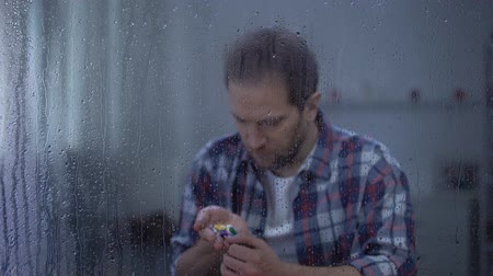 yağmur yağıyor : Desperate male holding pills in palm behind rainy window, suicide attempt