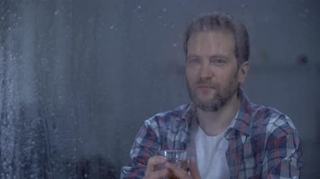 regozijo : Happy man drinking brandy alone on rainy day, celebrating career promotion Stock Footage
