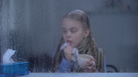 chřipka : Little girl suffering from flu behind rainy window sneezing and drinking hot tea