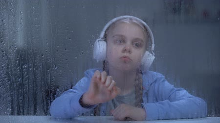 unalom : Bored girl in headphones listening to music behind rainy window, home alone Stock mozgókép