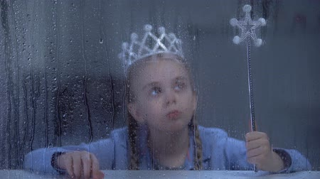 bóia : Upset little girl in crown with magic stick sitting alone behind rainy window