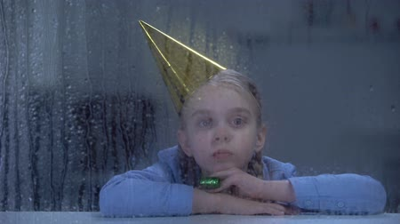 bóia : Lonely little girl in birthday hat with party blower looking in rainy window