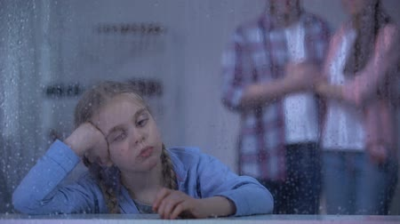 foster : Upset little girl behind rainy window, foster parents coming to adopt child Stock Footage