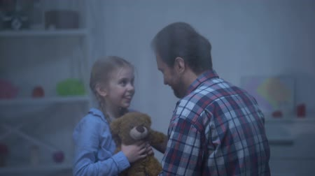 возвращение : Smiling girl with teddy bear hugging father, returning back home, rainy day Стоковые видеозаписи