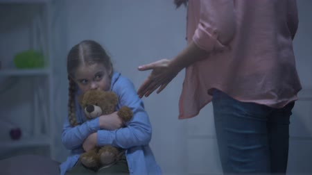 наказание : Angry mother screaming on daughter hugging teddy bear behind rainy window