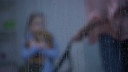 annoyance : Mother with belt threatening daughter hugging teddy bear behind rainy window Stock Footage