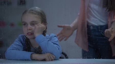 yağmur yağıyor : Mother screaming on little girl behind rainy window, bad behavior in school