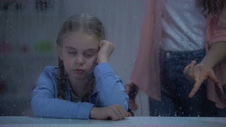 annoyance : Mother screaming on naughty little girl behind rainy window, problem child Stock Footage